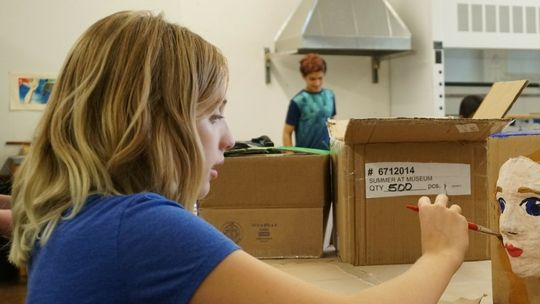 A young girl with blonde hair sits at a table. She is painting a plaster face that is attached to a cardboard box.