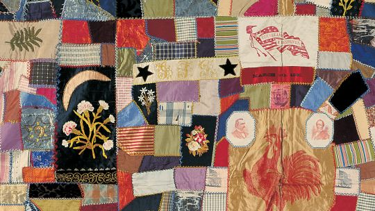 A patchwork quilt made up of various strips of fabric in many colors