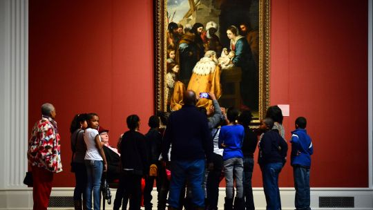 Group of visitors gathered around a painting