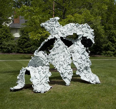 A large white sculpture with bumps stands outside on a grassy knoll.