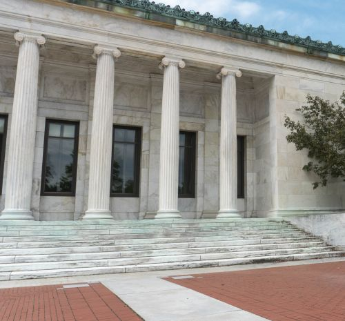A white marble building with four columns in front and a copper roof stands in front of a bright blue sky. There are steps leading up to the columns and a red brick patio in front. Two small trees with red buds are two the right of the columns.