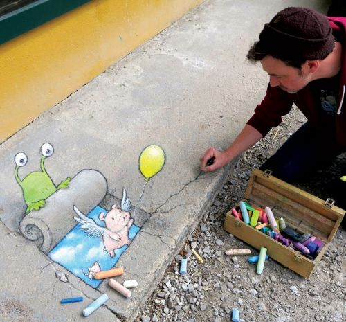 A man with dark hair sits on a sidewalk and is drawing a picture with colored chalk of a small pink pig with wings holding a yellow balloon. The man is wearing a knit cap and a maroon sweatshirt.