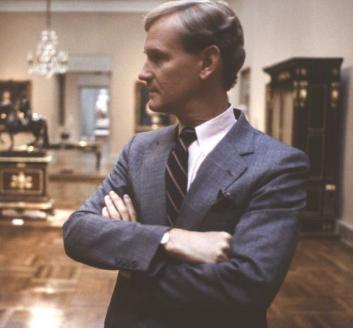 A young man in a blue suit stands in an art gallery with his arms crossed.