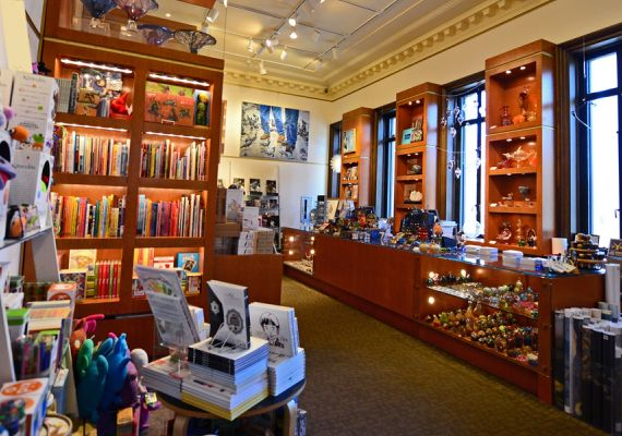 A store with tall brown wood cabinets full of books, toys and art