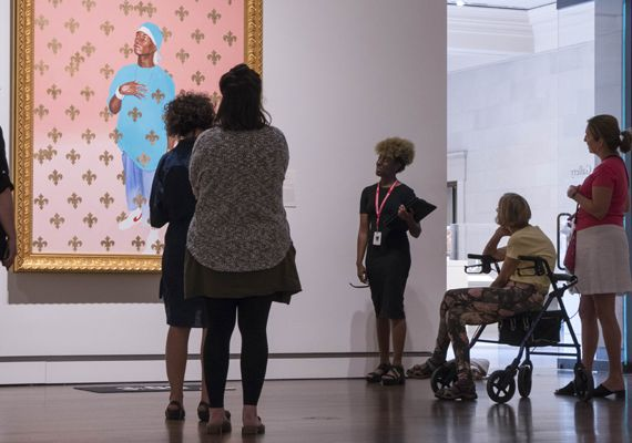 A young woman and an older woman in a wheelchair are looking at a portrait of a young man