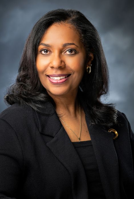 An African American woman is posing for a portrait. She has shoulder length black hair and is wearing a navy blue suit.