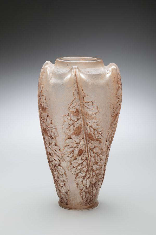 A pale white and rose colored vase has leaf-like designs molded vertically on its sides.