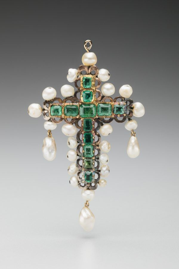 A small cross made of 13 square-cut Colombian emeralds set in gold and surrounded by natural pearls.