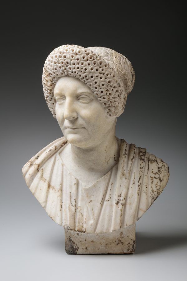 A marble bust of an older women with curly hair.