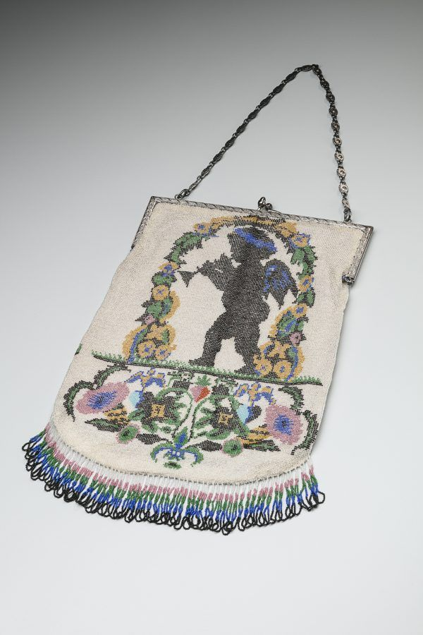 A long purse compoesd of white, pink, green, blue, yellow, and block glass beads. The design is of a cherub playing a trumpet.