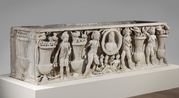 A sarcohpagus made of white marble. On the outside is a carved scene of urns and various Roman gods.