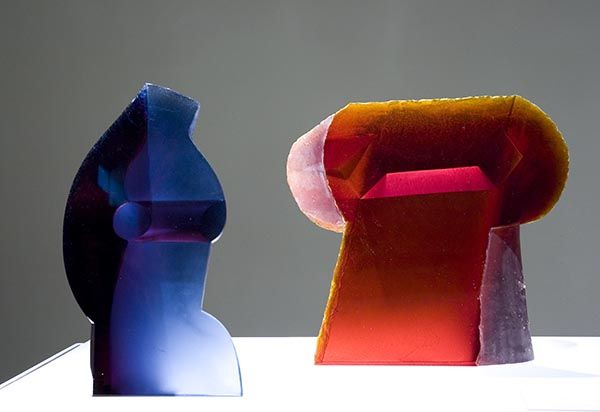 A blue sculpture made of glass and a red sculpture made of glass stand next to each other.