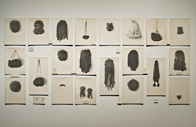 An array of vacant wigs and hairpieces from thick braids and weaves to smooth blond locks in black and white and printed on felt.