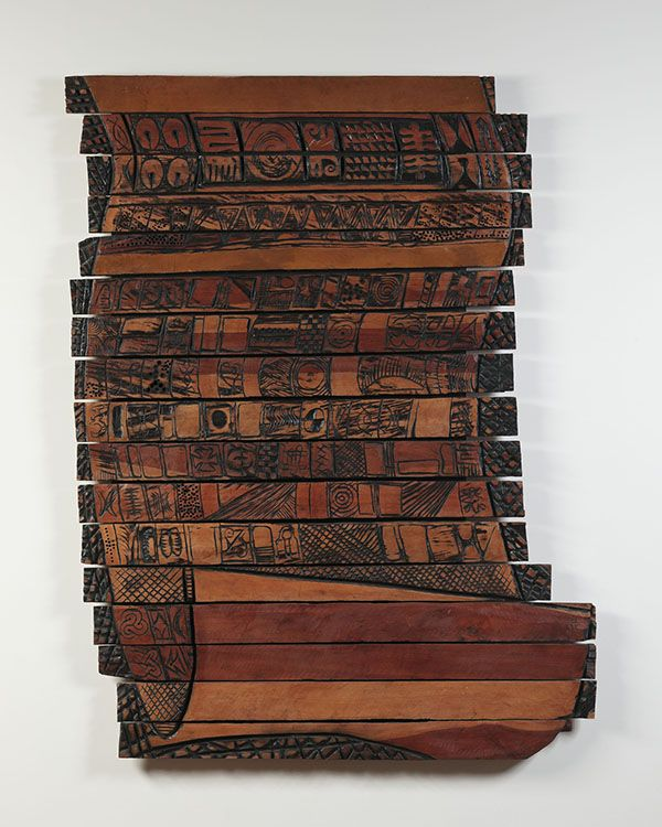 A flat wooden scroll made of brown wood with engraved and burned letters on it.