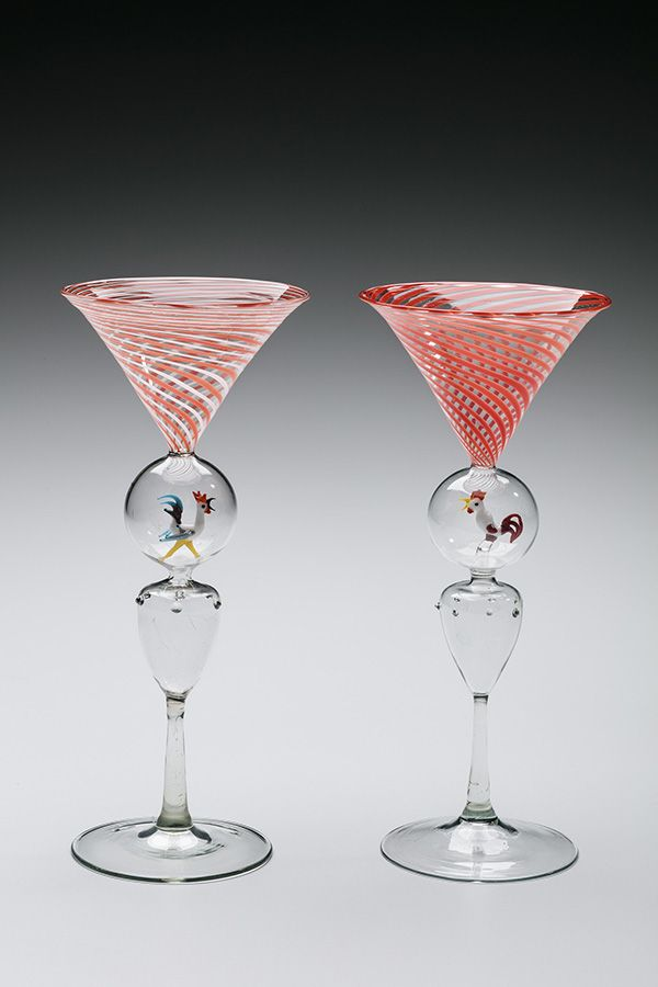 There are two martini glasses. The part that holds liquid is designed with orange stripes. The necks of the glasses include a clear marble. In the marbles are glass roosters.