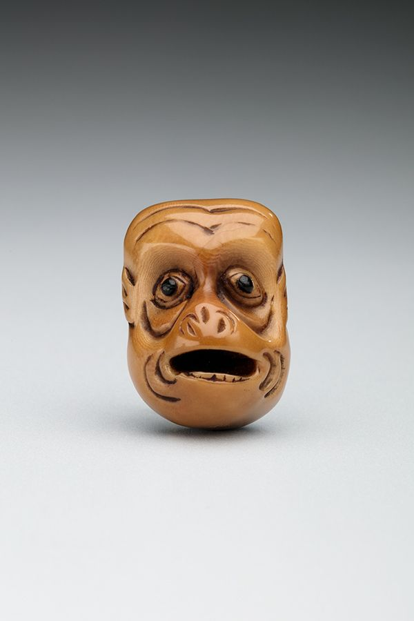 A small replica of a monkey's head carved from a palm nut
