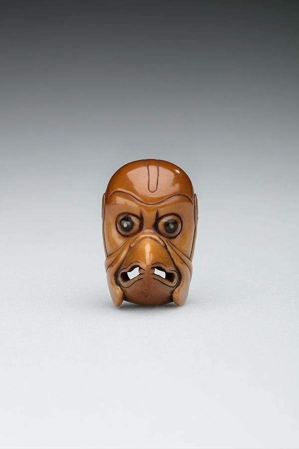 A small replica of the head of a half-bird, half-man mystical figure from Japan. It is carved from corozo nut.