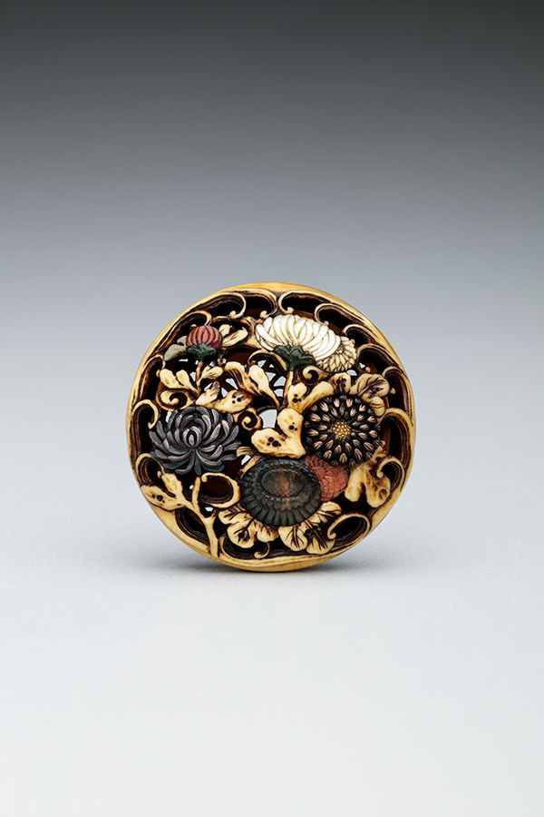 A small disk carved from ivory with flowers made of inlaid metals and mother of pearl.