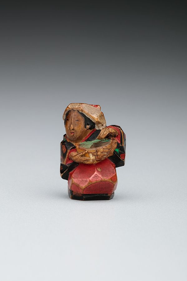 A small figure in the shape of a women. She is wearing a red kimono and is carrying a basket. The figure is carved from tea bush wood.