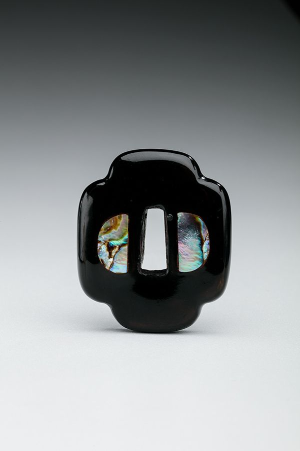 A small figure made of black lacquer and mother of pearl in the shape of a tsuba, the hand guard mounted on a Japanese sword.