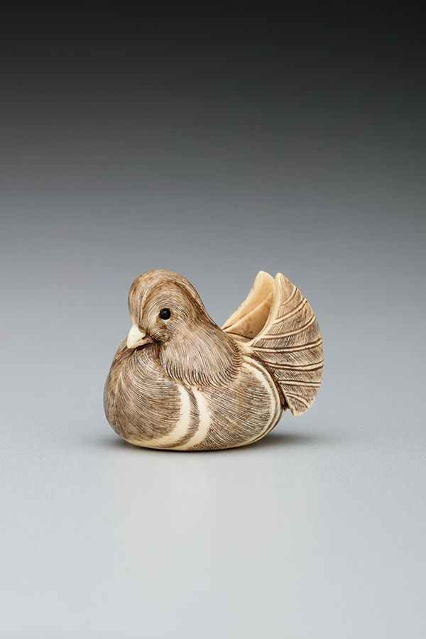 A small figure in the shape of a duck that is carved from ivory.