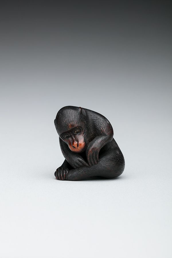 This is a picture of a small monkey-shaped figure. It is black in color and is carved from wood. The monkey is sitting down and leaning over in order to pick tiny bugs from its leg fur.