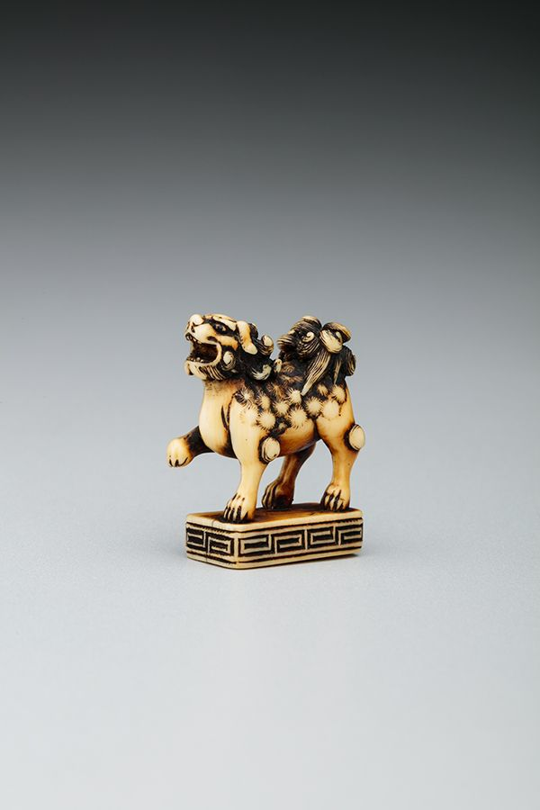 This is a picture of a lion-dog figure carved from ivory. The creature is standing on three legs; it is raising it's front right paw.