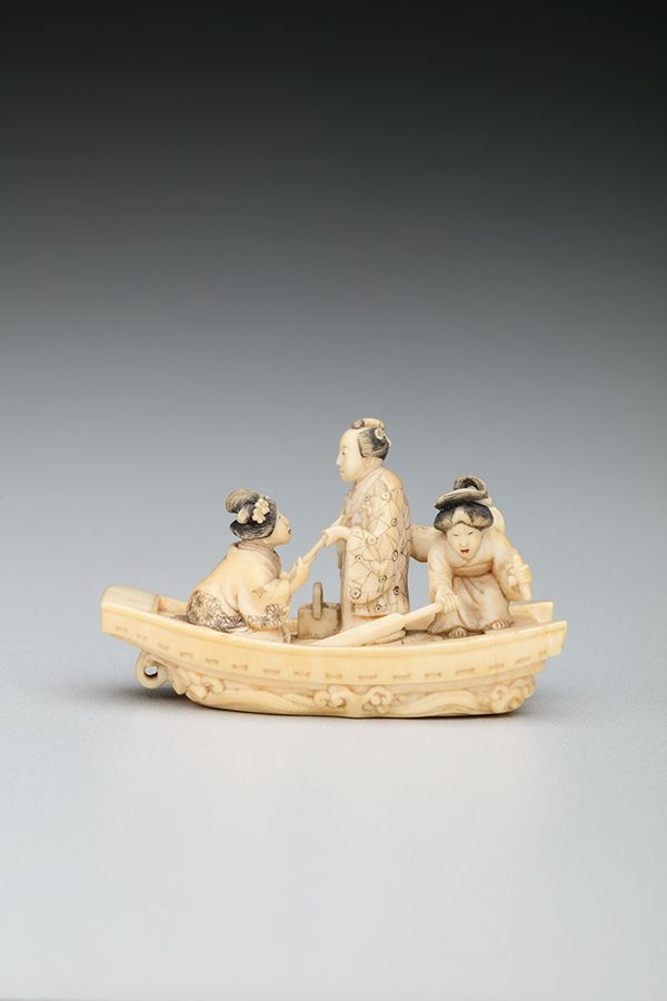 Two women and one man, all wearing kimonos, are situated in a small boat. This small figure is carved from ivory.