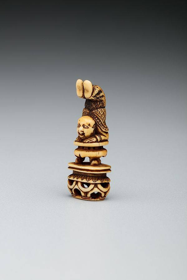 This small figure is carved from ivory and features a man balancing on his arms on top of a pedestal. His torso extends upwards and his feet hang over his head.