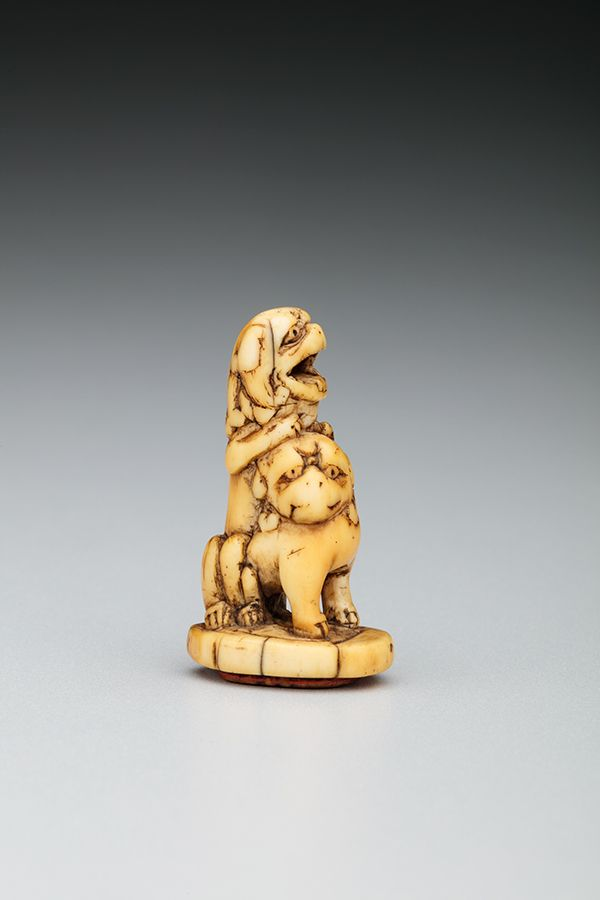 This small sculpture is carved from ivory and features two lion-dog creatures are wrestling.