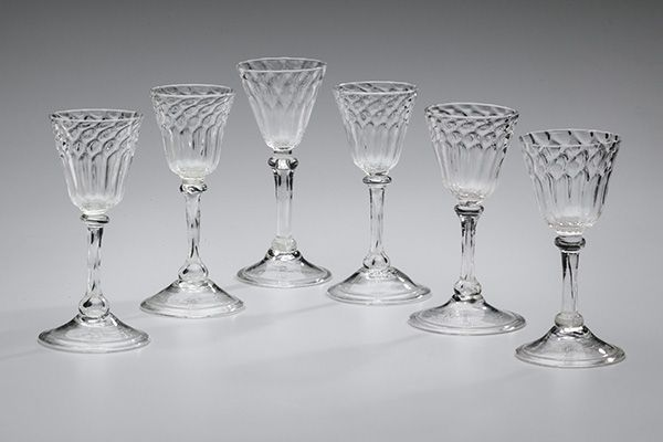 There are six glasses in a row. Each glass is made of clear glass. The top of the glasses are have a swirled pattern.
