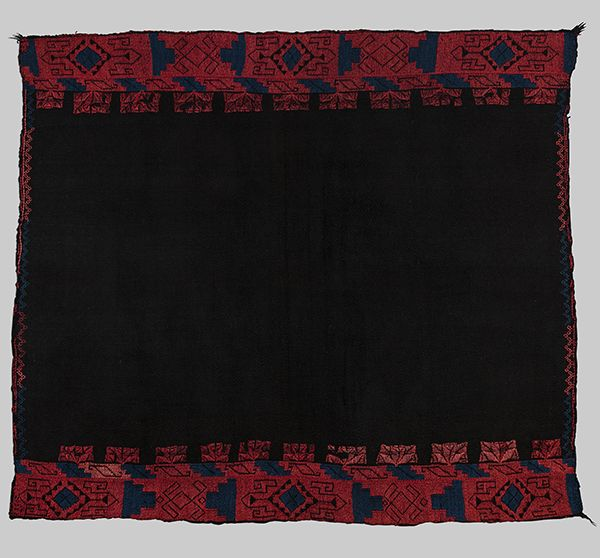 A woven manta made of black, red, and blue yards. The trim of the manta is a repeating pattern in red and blue. The rest of the manta is black.