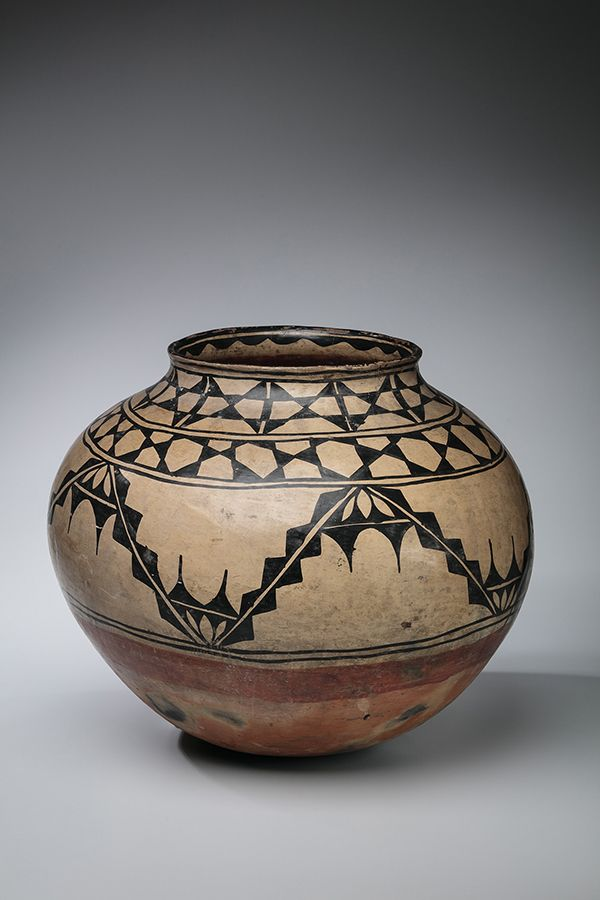 A large round clay pot that is a very light brown. It has various patterns circulating the top and middle in black. The bottom of the clay pot is reddish in color.