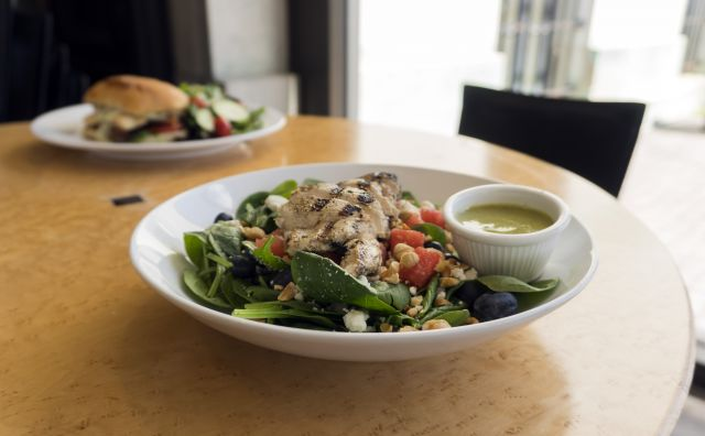A salad with strips of chicken on a large white plate.