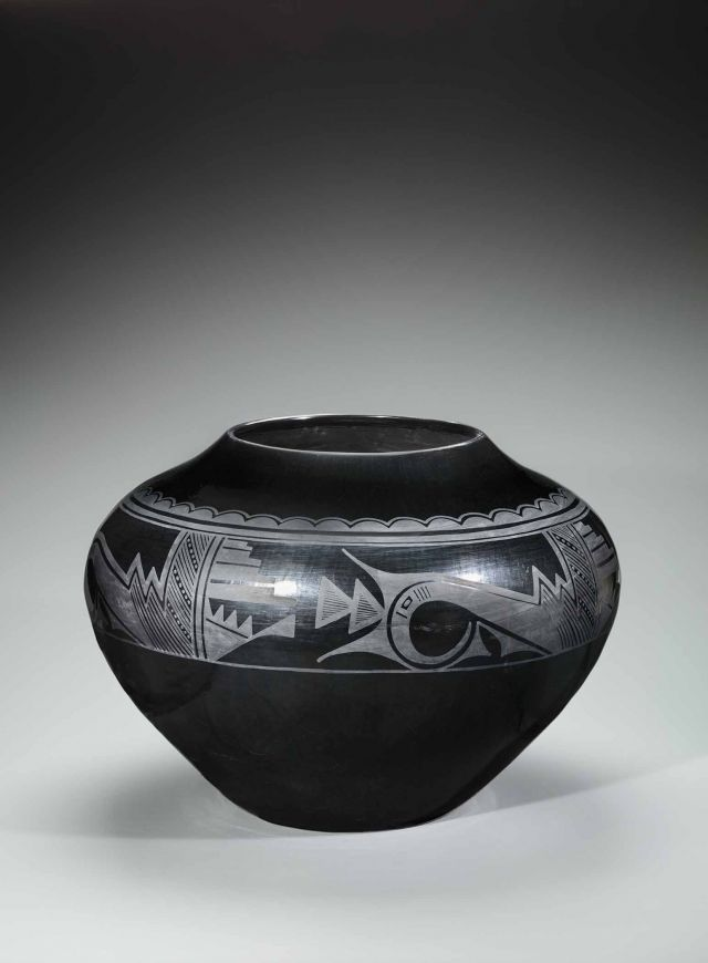 A black pot made from clay with white designs painted on it.