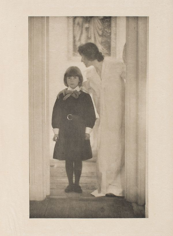 A black and white photograph of a mother with dark hair and her elementary school aged daughter wearing a dark dress and tights. They are standing in a doorway.