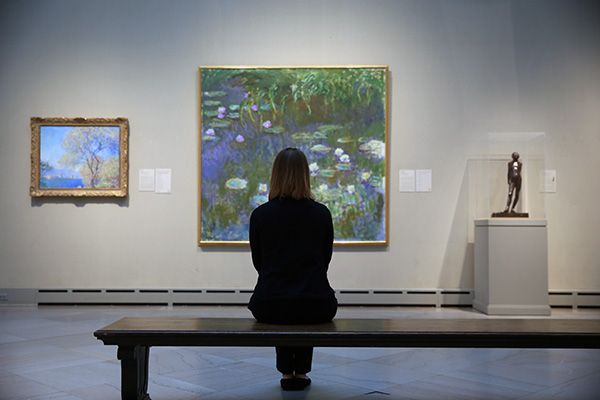 A young women sits on a bench with her back to the viewer, looking at a painting